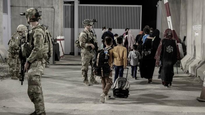 Flüchtlinge bringen sich, geschützt von US-Soldaten, am Internationalen Flughafen von Kabul in Sicherheit