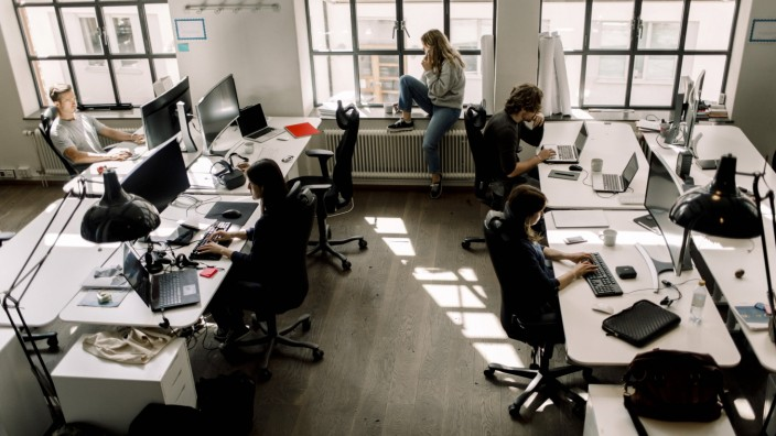 High angle view of coworkers working while female talking on phone in office Sweden, Stockholm, model released, property