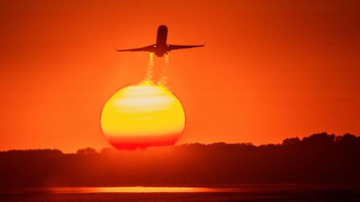 Eine Bombardier CR900 startet mit leuchtetendem Abgasstrahl vor untergehender Sonne