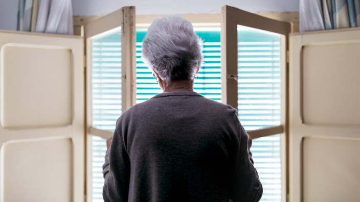 Gray haired woman standing in front of window at home Copyright: xSergioxVictorxVegax
