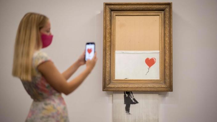 """""""Girl With Balloon"""": """"Die Liebe ist im Eimer"""": Banksys Werk, das mal """"Girl with Balloon"""" hieß, wird erneut versteigert."""