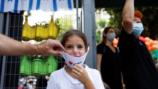 Und schnell noch die Maske auf: Vor einer Grundschule in Tel Aviv.