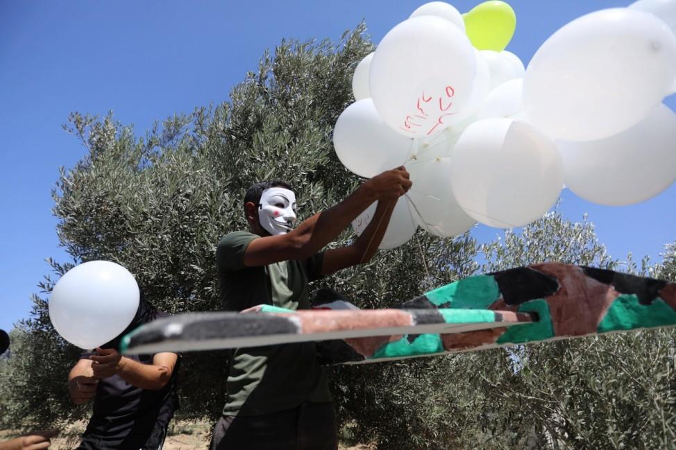 September 4, 2021, Jabalia, Gaza Strip, Palestinian Territory: Masked Palestinians prepare incendiary balloons near Jaba