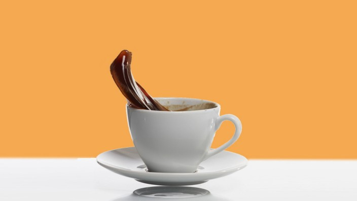Black coffee splashing out of white coffee cup in front of white background PUBLICATIONxINxGERxSUIxA