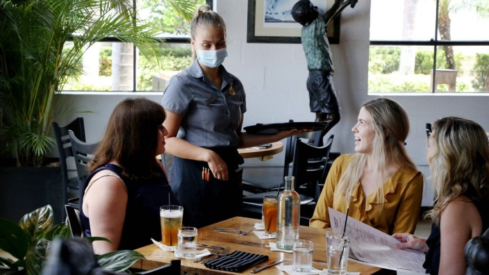 July 27, 2021, TAMPA, Florida, USA: Server Hanna Holt, center, discusses the lunch menu with Dana Nafe, of Tampa, left,