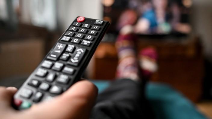 Mit der Fernbedienung vor dem Fernseher