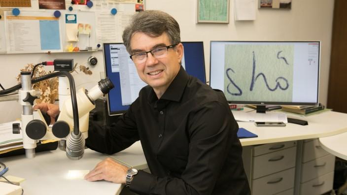 Erwin Sadorf, Schriftsachverständiger am  LKA, sitzt in seinem Büro vor einem Mikroskop.