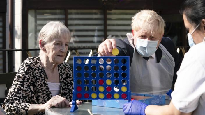 """Premier Boris Johnson spielt """"Vier gewinnt"""" während eines Besuchs in einem Pflegeheim im Londoner Stadtteil Stepney Green."""