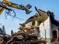 Bagger beim Abriss eines Hauses Deutschland Bayern Excavator demolishing a house Germany Bavaria