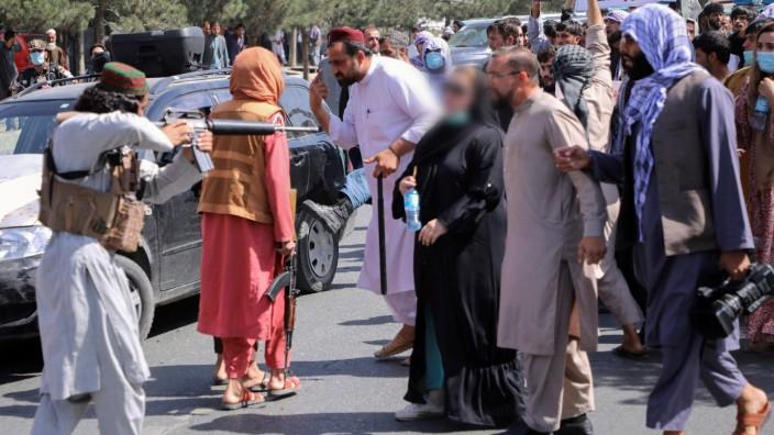 Protest vor den Gewehrläufen: Mit der Waffe bedroht ein Milizionär der Taliban eine Demonstrantin in Kabul.