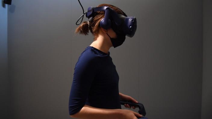Netzkolumne: Liefert die virtuelle Realität den Zugang zu neuen Welten - oder lediglich neue Scheuklappen, um die Leute ruhigzustellen? Eine Besucherin mit VR-Brille beim Filmfestival von Venedig.