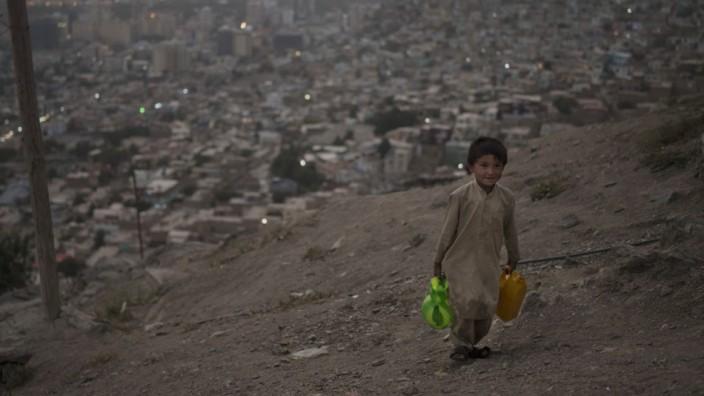 Afghanistan: Mitte nächsten Jahres könnten fast alle Afghanen unter die Armutsgrenze fallen: Ein kleiner Junge schleppt Wasser auf den Hügeln von Kabul, eine Szene vom vergangenen Wochenende.