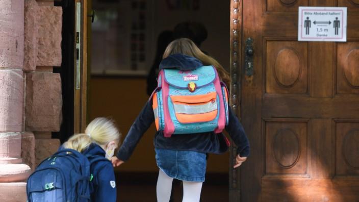 Corona in Deutschland: Zwei Schülerinnen betreten ein Schulgebäude