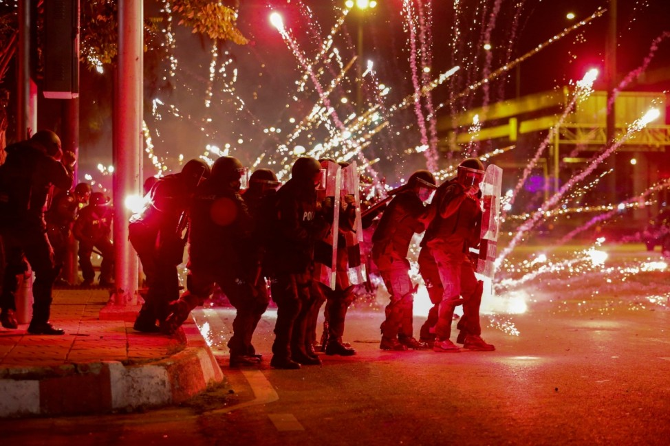 Fireworks thrown by anti-government protesters explode in front of a line of riot police officers during an anti-government protest in Bangkok