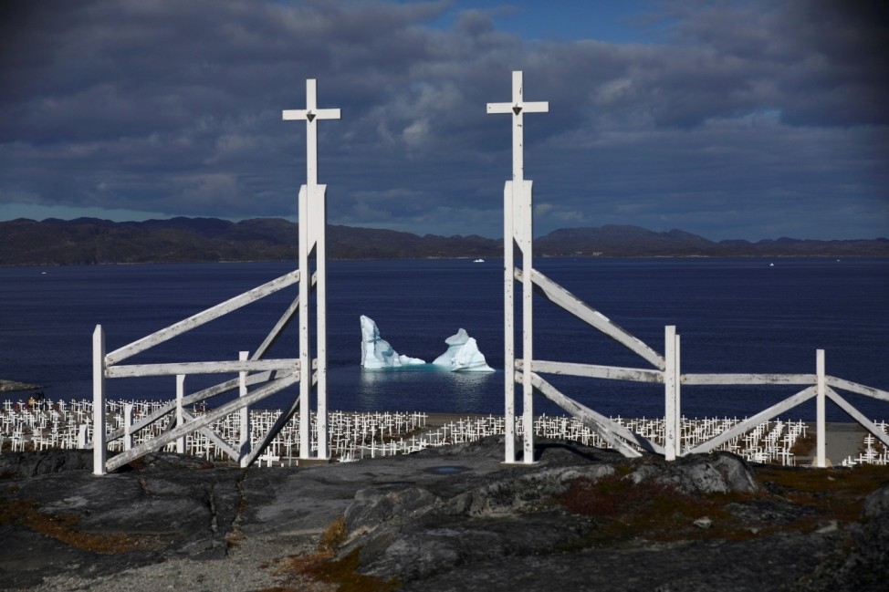 An iceberg is seen at the shore of a graveyard in Nuuk
