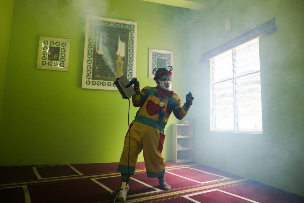 Shaharul Hisam bin Baharuddin, 43, dressed as a clown disinfects a prayer room inside a shopping mall in Taiping