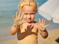 Selective focus on a little girl s sandy hands at the beach on a sunny day, Model released Copyright: xPhilippexDegroote