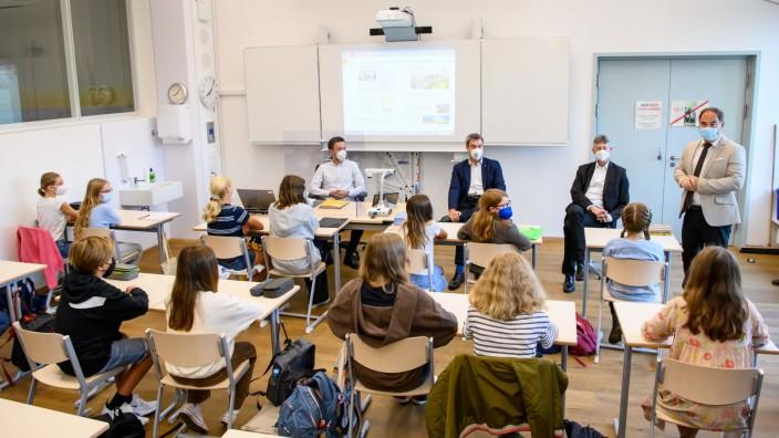 """""""Wir wollen, dass es euch gut geht"""", sagte Ministerpräsident Söder (blauer Anzug) zur Klasse 7d. Söder und Piazolo sitzen im Klassenraum vor den Schülern."""