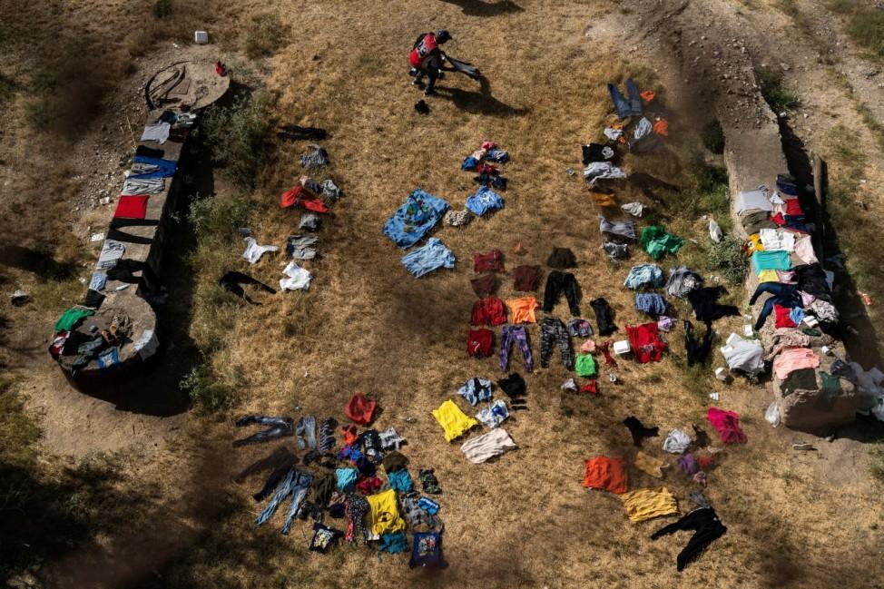 Asylum-seeking migrants wait to be processed under the international bridge in Del Rio, TX