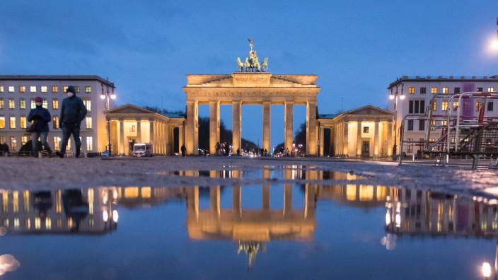Spiegelung des Brandenburger Tors in einer Pfütze Deutschland, Berlin - 13.01.2021: Nach dem Regen spiegelt sich das Br