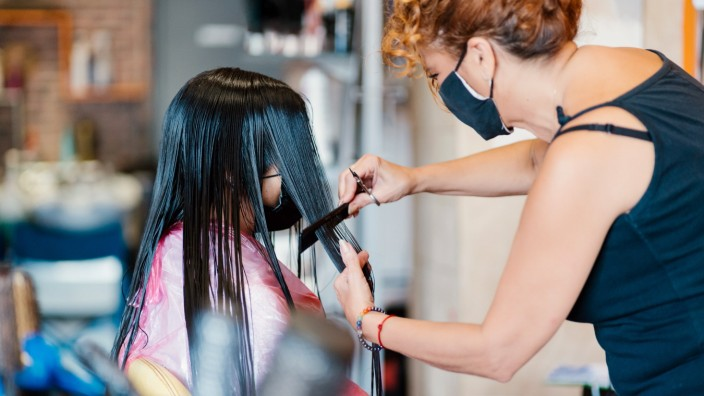 Woman in the hairdresser s with a mask, cutting her hair Valencia, Valencian Community, Spain PUBLICATIONxINxGERxSUIxAUT