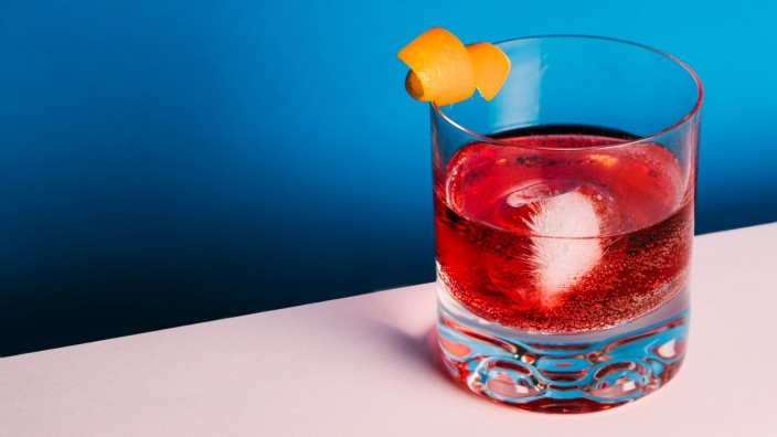 Glass of bitter alcoholic Negroni cocktail served with ice and orange peel on light surface Copyright: xRamonxLopezx