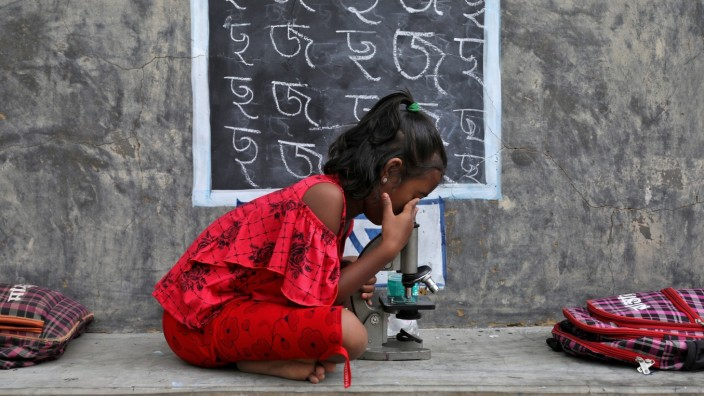 A girl uses a microscope as she attends an open-air class outside a house with its walls converted into black boards at Joba Attpara village