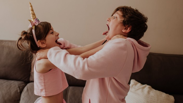Side view of brother and sister in pink outfits strangle each other while fighting near sofa at home Copyright: xGalaxMa