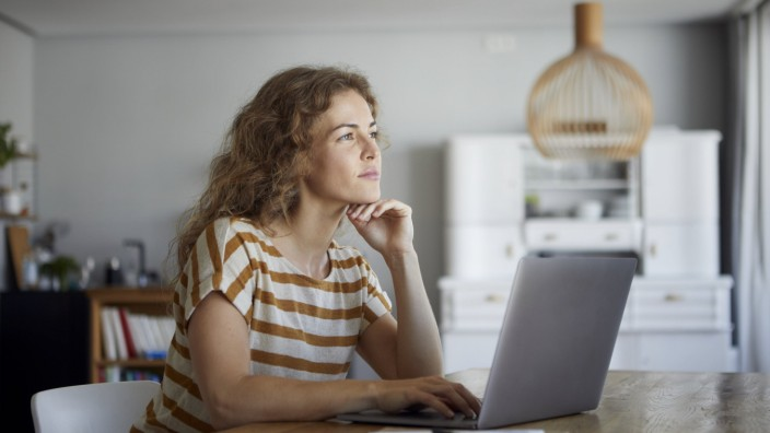 Thoughtful woman with head in hands using laptop while sitting by table at home model released Symbolfoto property relea