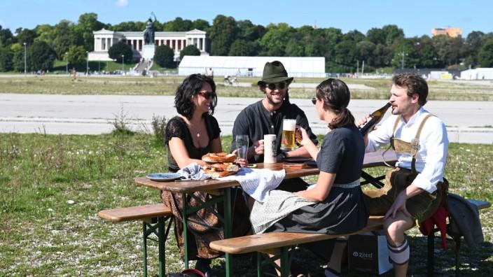 München heute: Ozapft is: Mittags um halb eins sitzen einige auf der Wiesn, manche haben Bierbänke mitgebracht.