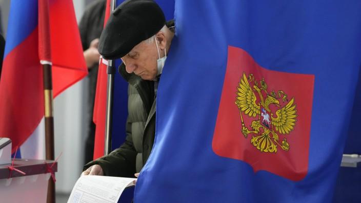 Duma Wahl: Ein Russe überprüft bei der Parlamentswahl in Sankt Petersburg noch einmal seinen Stimmzettel.