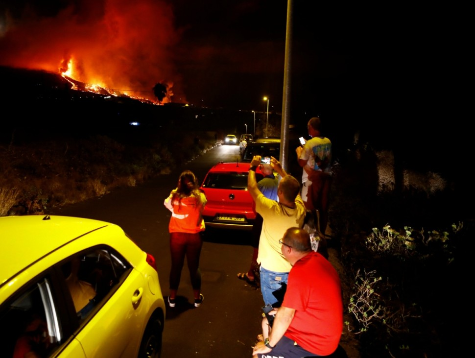 REsidents watch lava following the eruption of a volcano in Spain