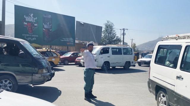 """Verkehr in Kabul: 14 Stunden am Tag steht Ainullah Razooli auf der Kreuzung vor dem stadtbekannten gut 100 Jahre alten """"Turm der Befreiung""""."""