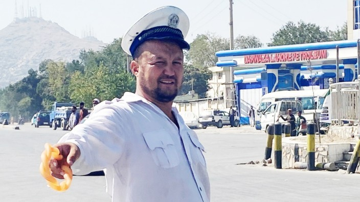 Verkehr in Kabul: Harter Job für wenig Geld: Ainullah Razooli, Verkehrspolizist in Kabul, trägt bei der Arbeit eine Art Gummiknüppel, mit dem er auf Autos schlagen kann.