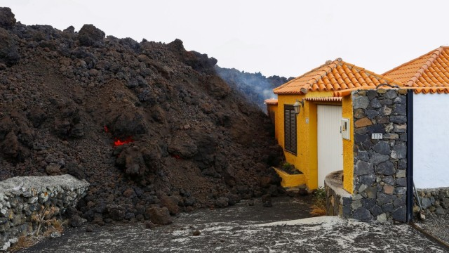 Lava reaches a house following the eruption of a volcano in Spain