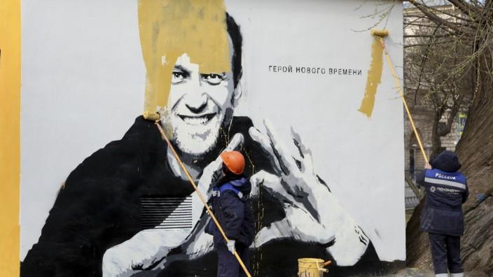 Russland: Arbeiter in Sankt Petersburg übertünchten schon im Frühjahr ein Poster des Oppositionellen Alexej Nawalny, der im Gefängnis sitzt.