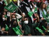 Saudi Arabian football fans hold up their national flags to show support for Saudi Arabia national f; Saudi Arabian women cheer after Saudi Arabia routed North Korea 4-0 in Asian Cup