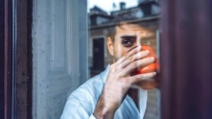 Young man holding cup looking out of window model released Symbolfoto property released EHF00976