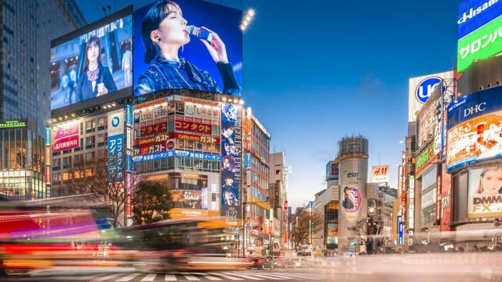 Shibuya Crossing Langzeitbelichtung Autos fahren über Kreuzung bunte Schilder und Leuchtreklamebe