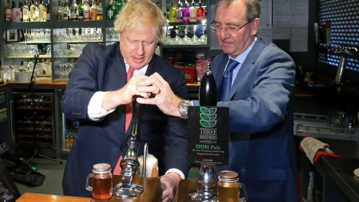 Großbritannien und der Brexit: Boris Johnson, hier mit dem Abgeordneten Paul Howell (r.), will zum imperialen System für Gewichte und Maße zurück. Am Bier ändert das nichts, das gab es im Pub schon immer als Pint (= 0,5683 Liter).