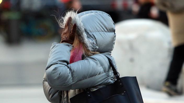 Frau hält sich zum Schutz vor den Sturmböen die Hände vor ihr Gesicht in der Innenstadt Frankfurt H