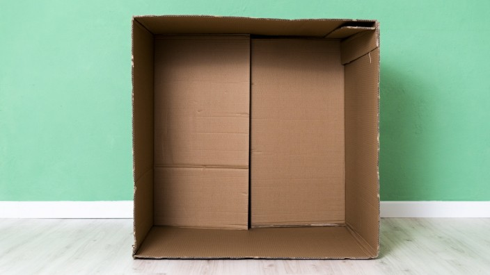 Empty cardboard box against green wall in apartment property released GIOF10763