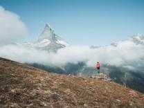 Yong woman standing on rock in front of Matterhorn above clouds Zermatt, VS, Switzerland PUBLICATIONxINxGERxSUIxAUTxONLY