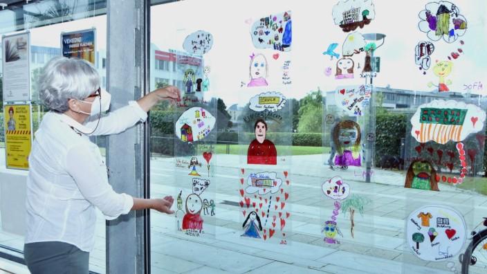 Germering: Bemalte Folien, die von beiden Seiten des Fensters sichtbar sind, hängt Margarita Moroder in der Stadtbibliothek auf.