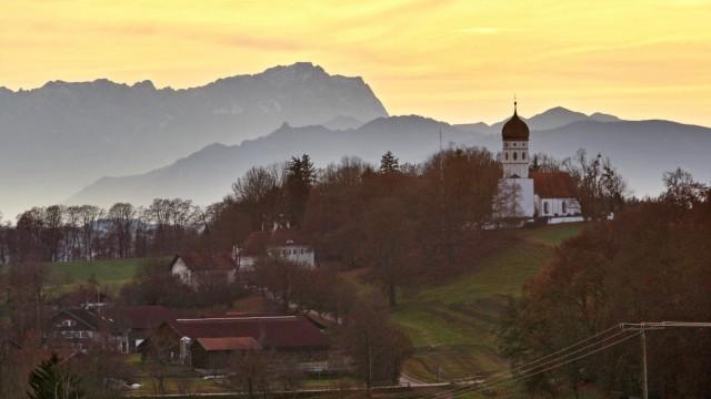 Bevölkerungsboom: Anziehungskraft: Es gibt im Landkreis schöne Flecken, so wie hier im Münsinger Ortsteil Holzhausen, mit Zwiebelturm-Kircherl und Zugspitze. Immer mehr Menschen siedeln sich in den Gemeinden im Norden und im Süden an. Deren Entwicklung soll mit Hilfe der Regionalplans gelenkt werden.
