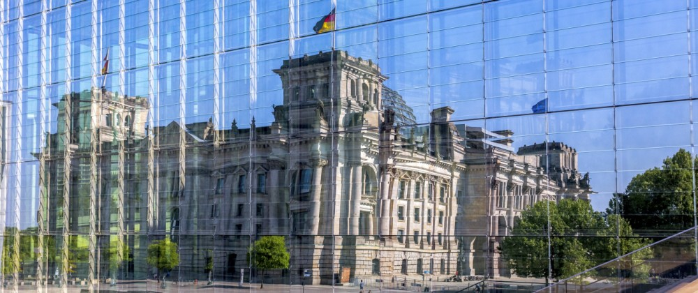 Germany Berlin Reichstag building mirrored in glass facade of Marie Elisabeth Lueders Building PUB
