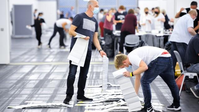 Ticker zum Wahlsonntag: Nie haben so viele Münchnerinnen und Münchner per Brief gewählt. Die Stimmen sortieren die Helfer erst einmal am Boden.