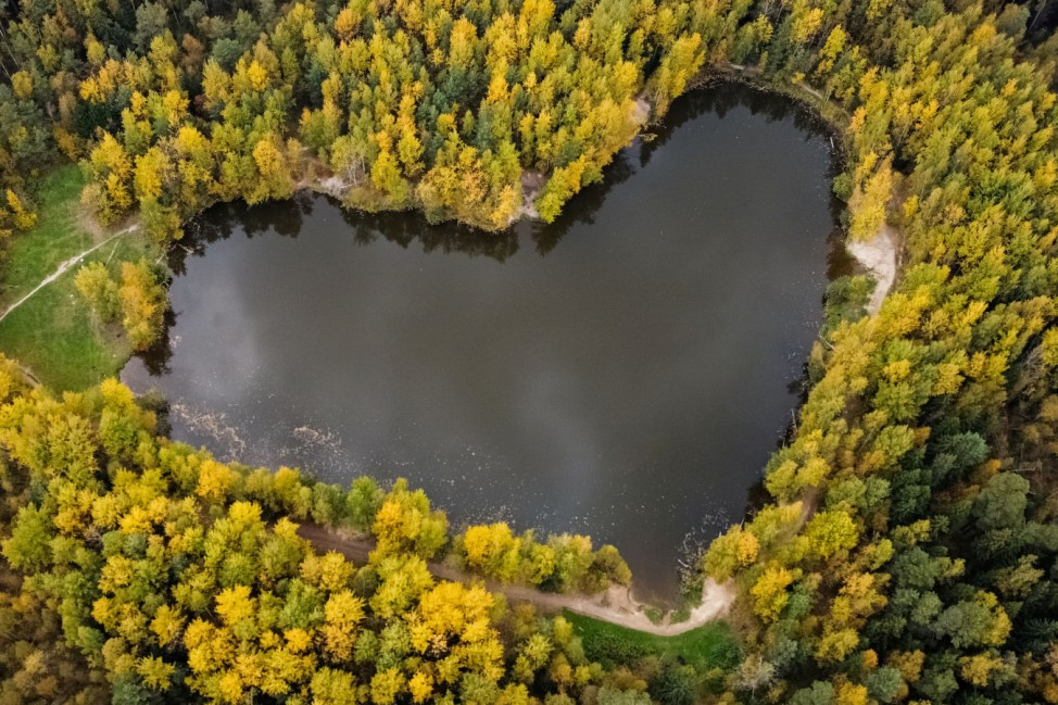 A lake in a shape of a heart is seen surrounded by autumn-coloured trees outside Balashikha