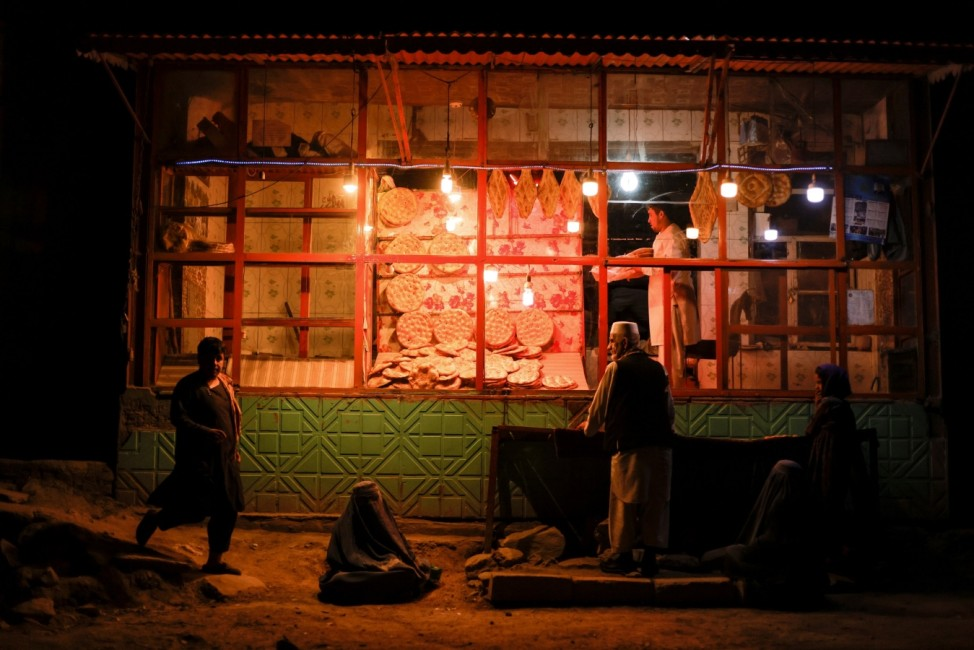 Women wearing burqas sit in front of a bakery in Kabul
