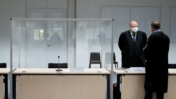The defendant's lawyer Wolf Molkentin speaks to a man next to the empty seat of the accused 96-year-old former secretary to the SS commander of the Stutthof concentration, in Itzehoe